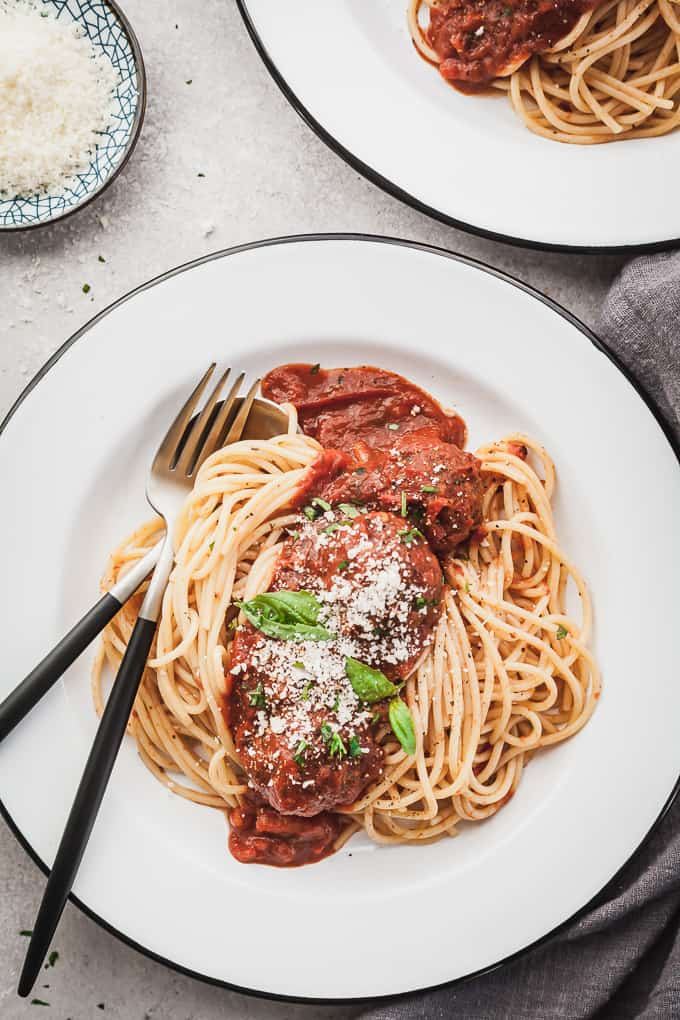 a plate of eggplant meatballs with spaghetti with a fork and spoon
