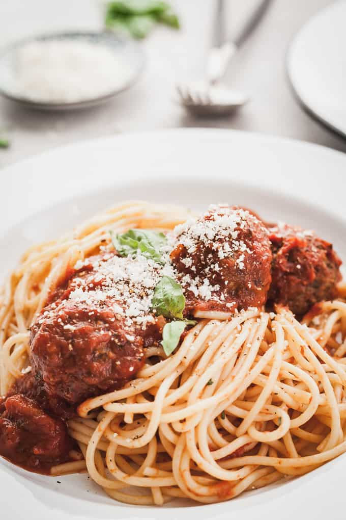 close up of eggplant meatballs with spaghetti on a white plate