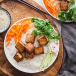 a white plate with tofu, rice noodles, and veggies