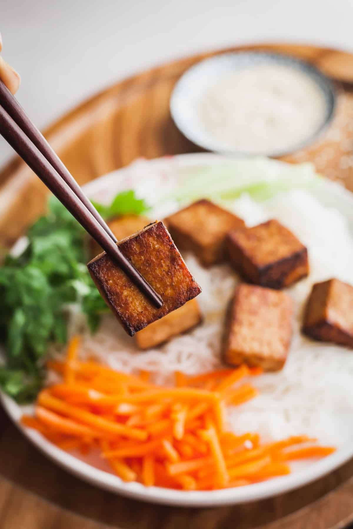 chopsticks holding a piece of perfectly cooked tofu