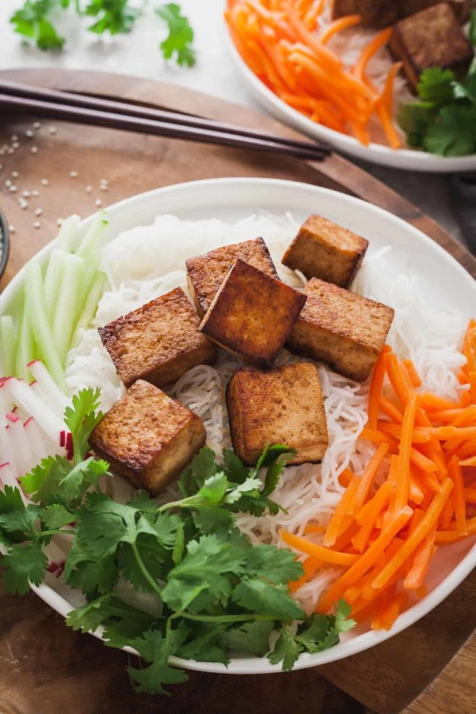 sauteed tofu on a bed of noodles with salad
