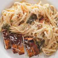 fettuccine alfredo with cajun tofu on a plate with a fork