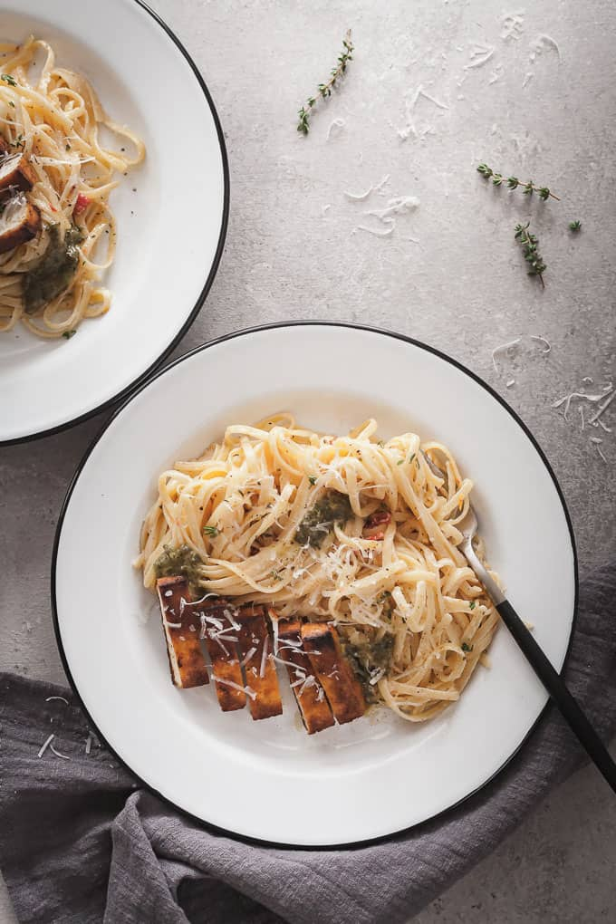 two plates with fettuccine alfredo and cajun tofu with a fork and napkin