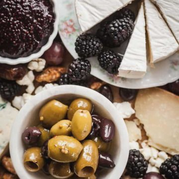 a bowl of mixed olives on a cheese board with fruit and jam