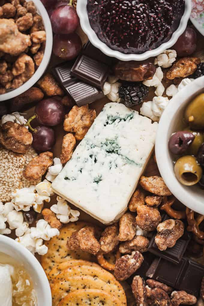 blue cheese at the center of a cheese board surrounded by nuts, chocolate, jam, and olives