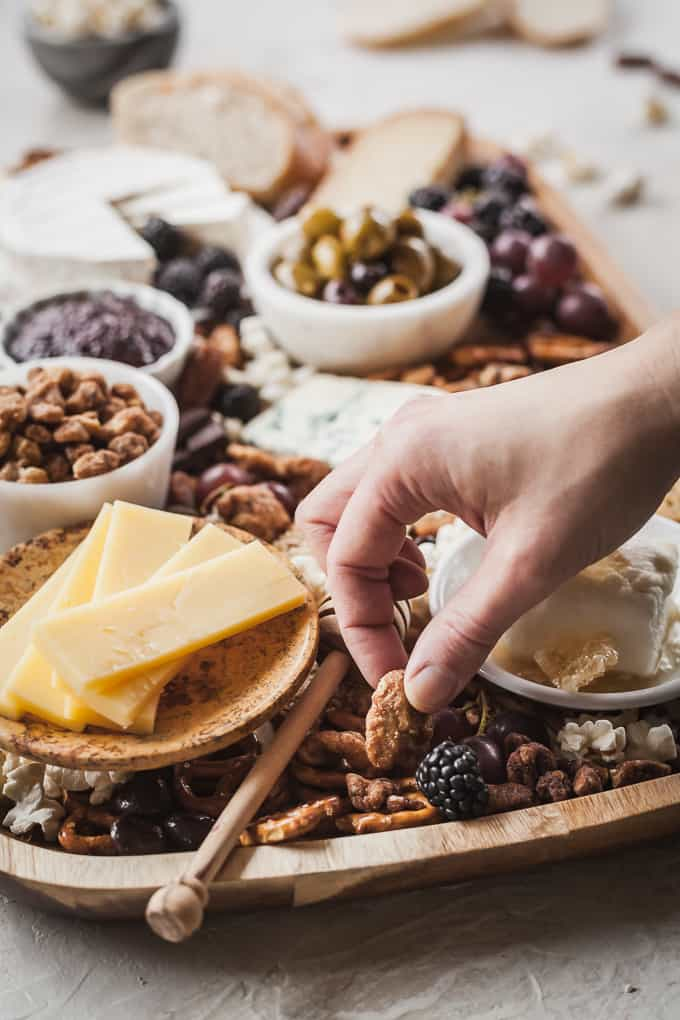 a hand grabbing a glazed nut from a sweet and salty cheese board