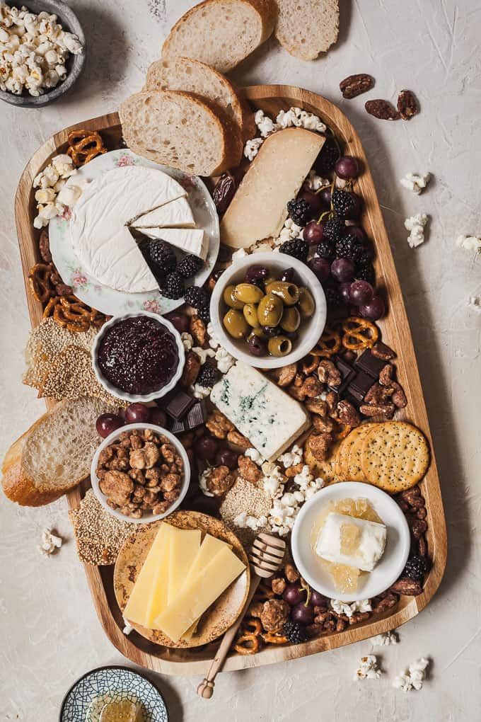 a cheese board full of sweet and salty snacks