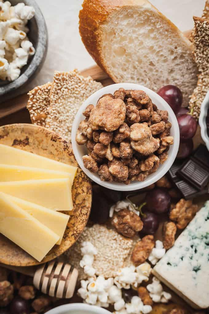 cheese, crackers, glazed nuts, and chocolate on a cheese board