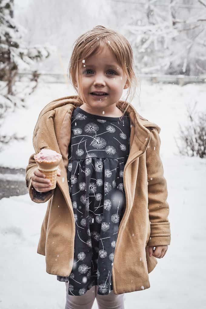 little girl in the snow with an ice cream cone