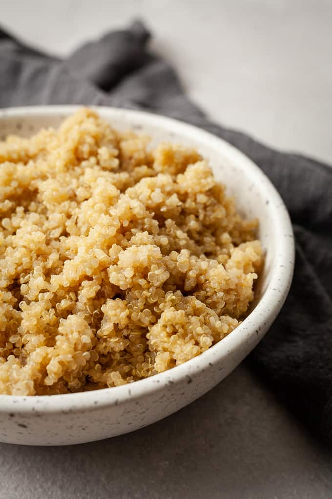 a bowl of quinoa with a dark napkin on a grey background