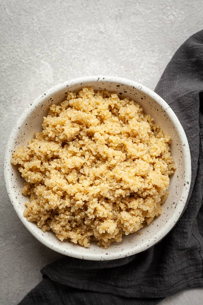 a speckled bowl with quinoa and a dark napkin on a grey background