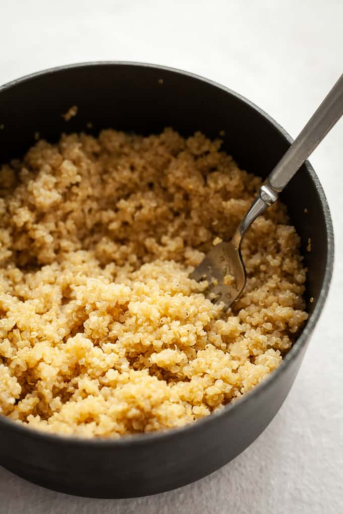 a pot of cooked quinoa with a fork in it