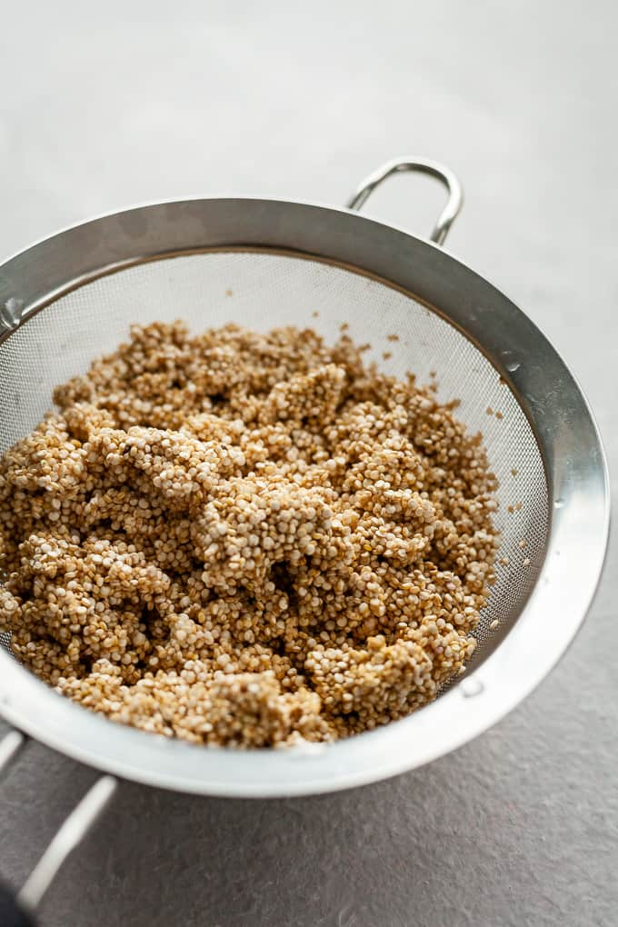 a fine mesh sieve with uncooked quinoa