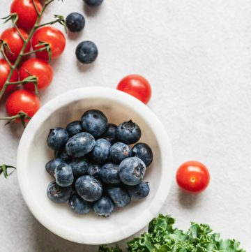 a white bowl of blueberries with cherry tomatoes and kale