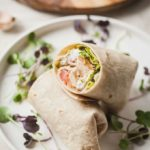 white plate with a vegetarian chciken caesar wrap cut in half