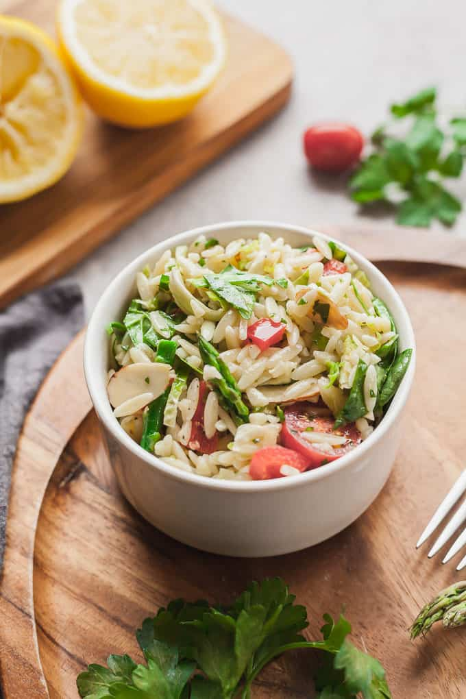 angled photo of a white bowl of vegan orzo pasta salad on a wood tray