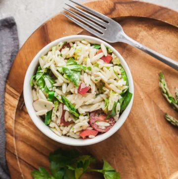 overhead photo of a white bowl of vegan orzo pasta salad on a wood tray with fork, parsley, and lemon