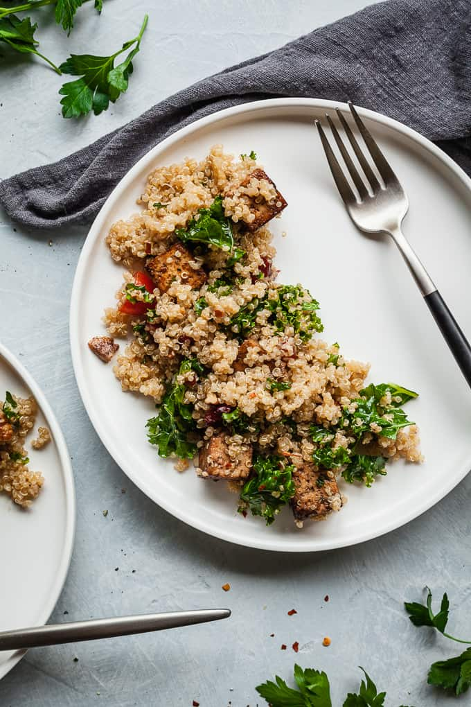 vegan quinoa salad with balsamic tofu on a white plate with fork and napkin