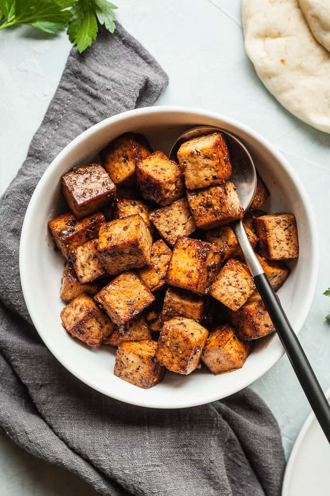a bowl of balsamic tofu with a spoon in it