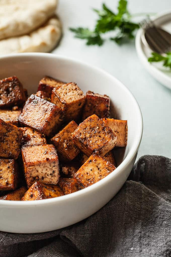 a bowl of balsamic tofu with a napkin, bread, and herbs