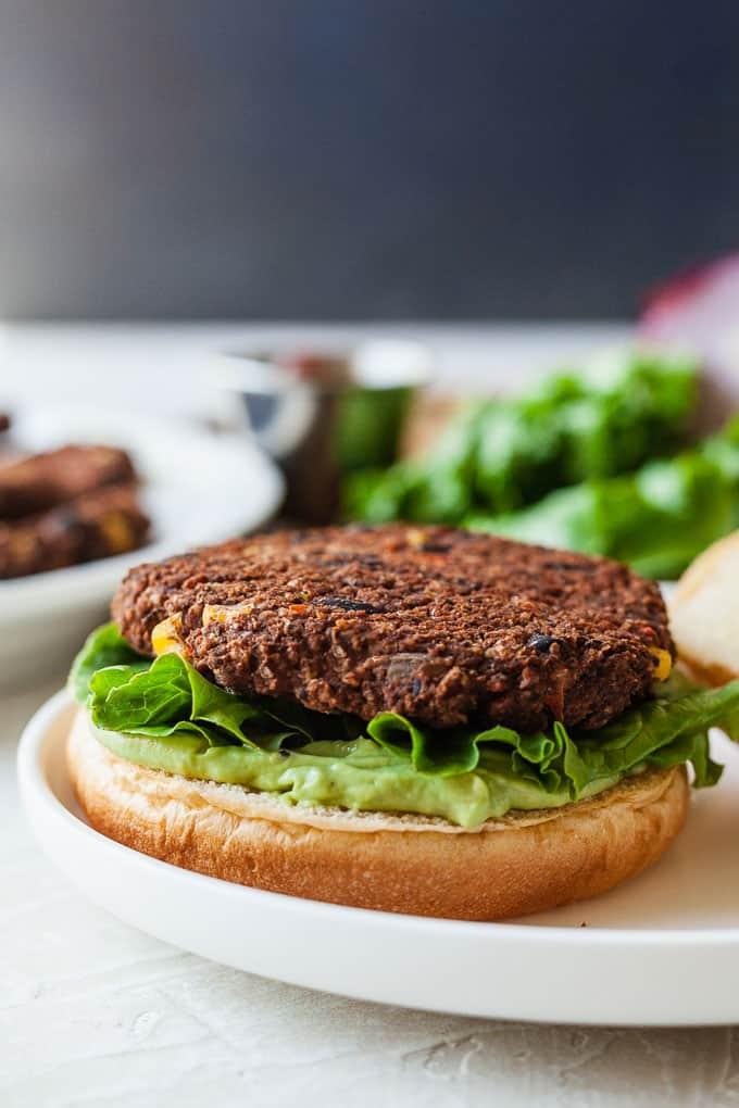 a black bean burger on a bottom bun with lettuce and avocado