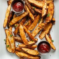 crispy oven baked potato wedges in a white pan with two bowls of ketchup