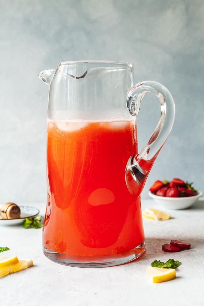 a tall pitcher of strawberry lemonade
