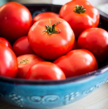 a blue bowl holding tomatoes