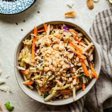 a bowl of Asian slaw with a small dish of black sesame seeds and a cloth napkin