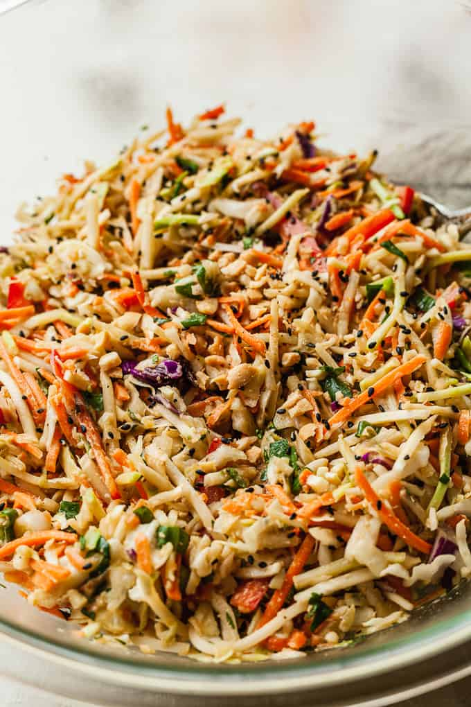 a close up photo of a big bowl of cilantro lime slaw with peanut butter dressing