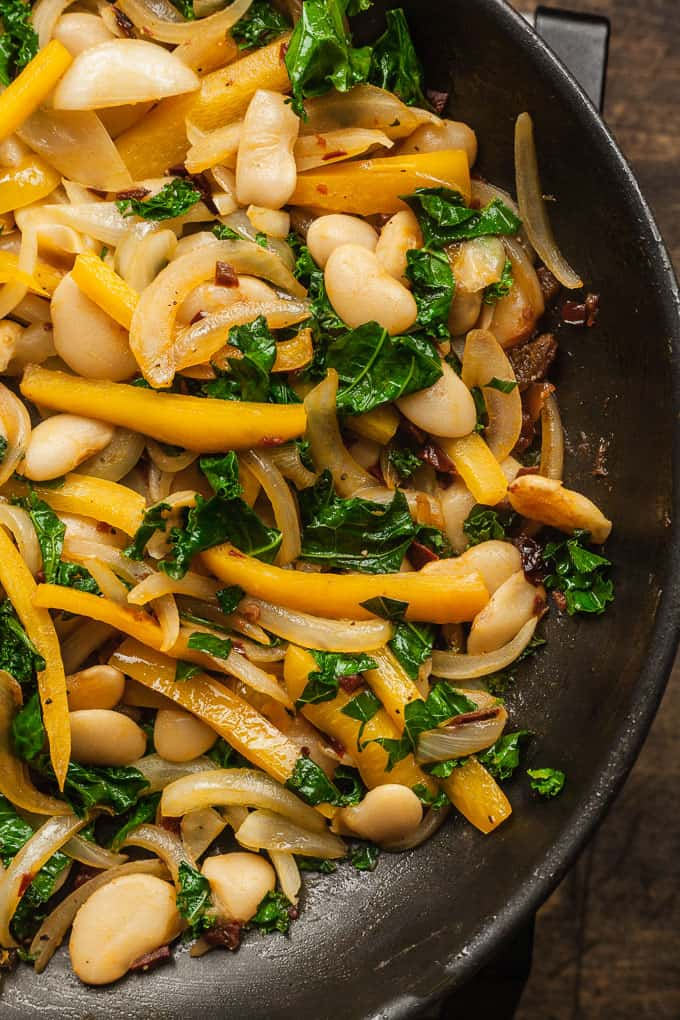 a frying pan with cooked onions, bell pepper, kale, and butter beans