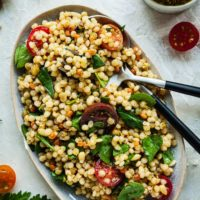 israeli couscous salad in a platter with a spoon and fork