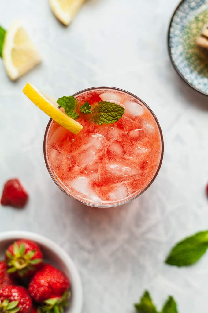 a glass of strawberry lemonade with mint, strawberries, and lemons