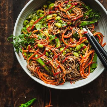 a bowl of soba noodle salad on a dark wood table