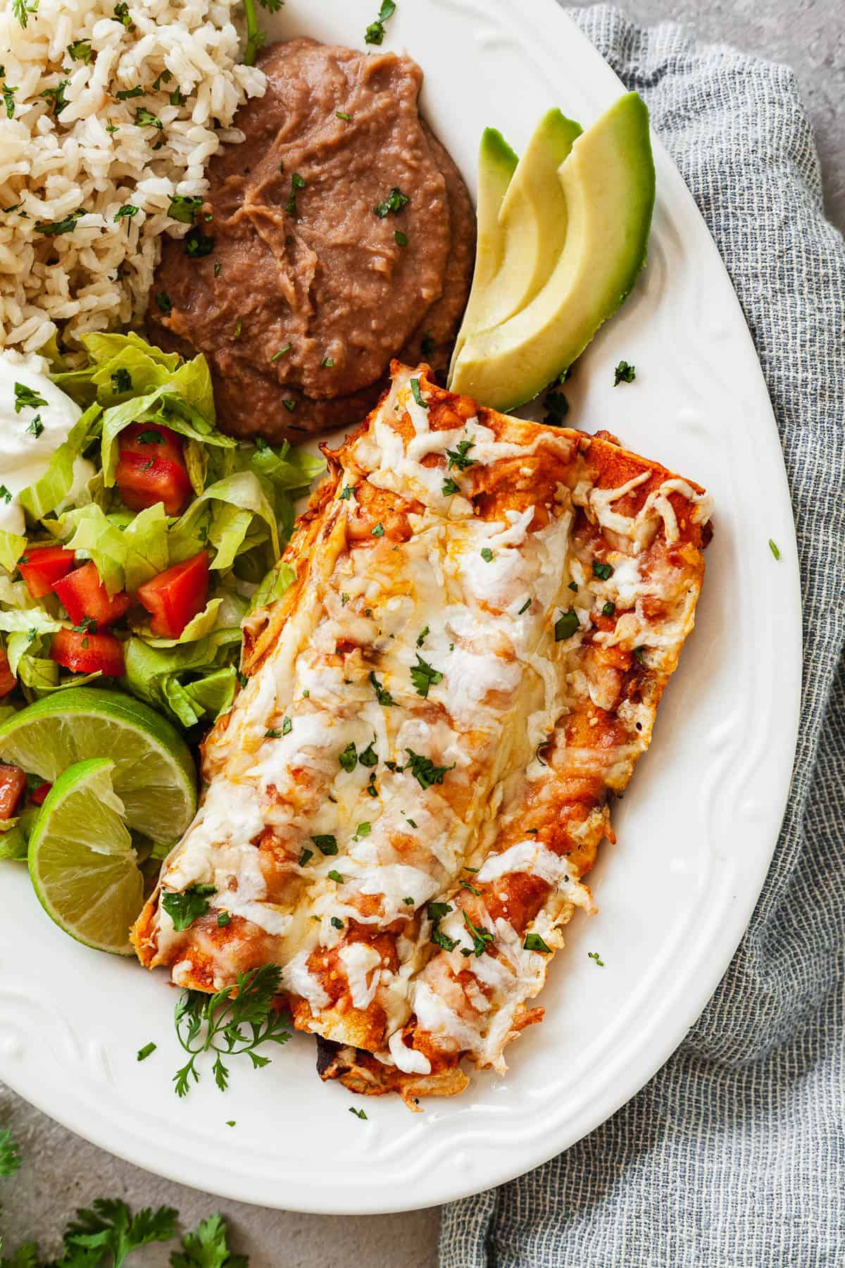 cheesy enchiladas on a plate with salad, rice, and beans