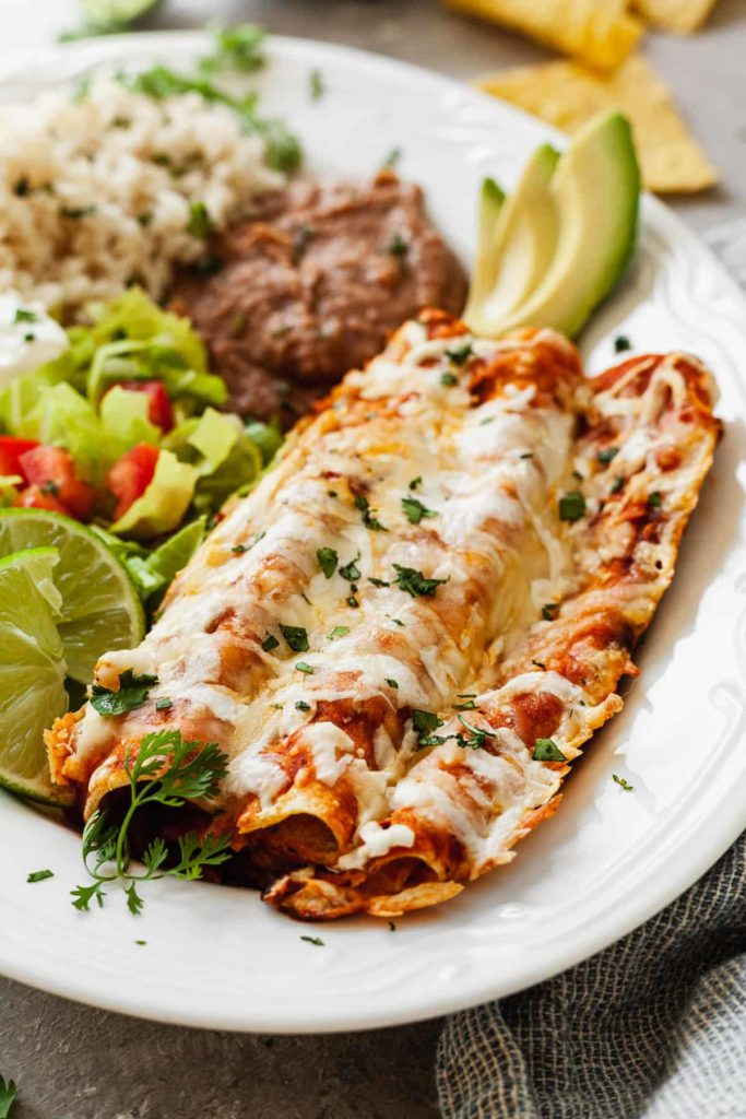 cheese enchiladas on a plate with salad, rice, and beans