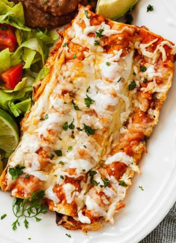 cheese enchiladas on a plate with salad and limes