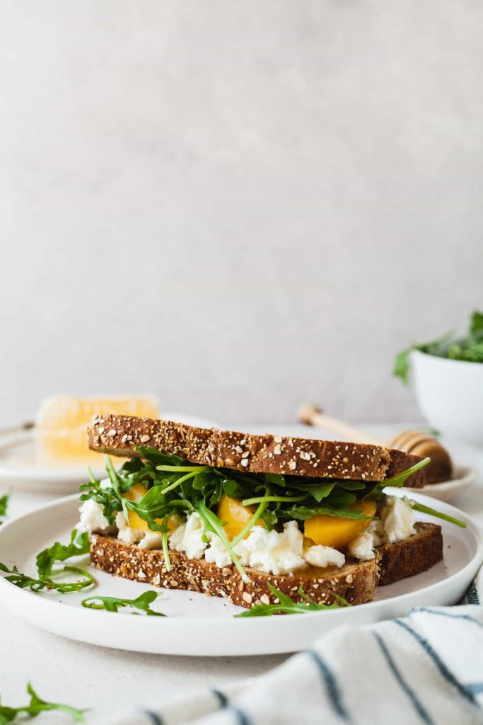 a peach, arugula, and goat cheese sandwich on a white plate with a striped napkin