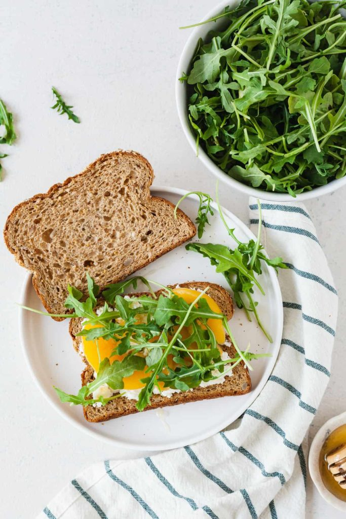 an open sandwich on a white plate with arugula, honey, peach slices, and goat cheese