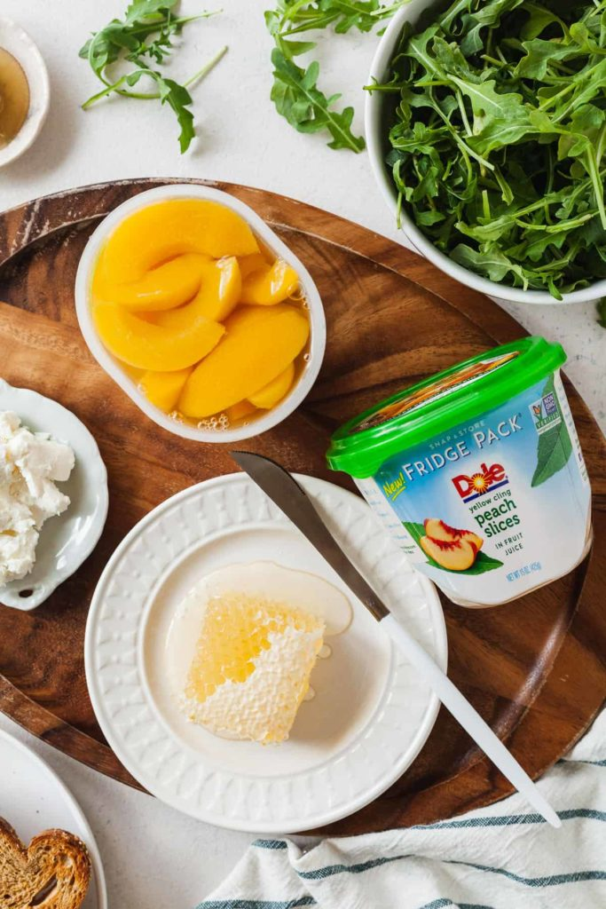 overhead photo of honeycomb on a white plate near two packages of peaches, some goat cheese, and a bowl of arugula