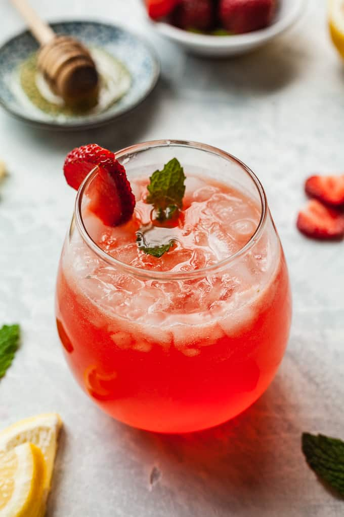 a glass of strawberry vodka lemonade cocktail with honey, strawberries, and lemons