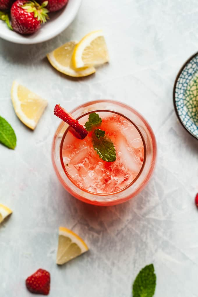 overhead photo of a glass of strawberry lemonade with vodka in it, lemons and mint around