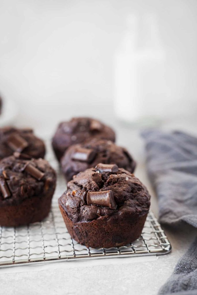 double chocolate zucchini muffins on a cooling rack with a napkin and glass of milk