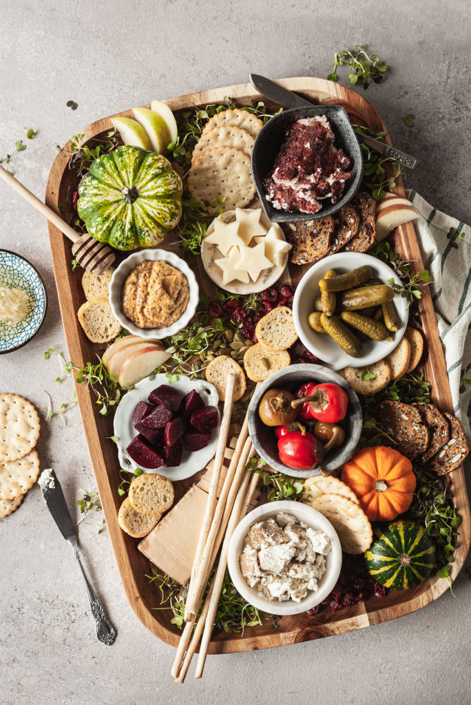 overhead photo of a fall cheeseboard with cheese, crackers, and pickled veggies