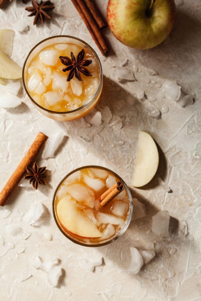 overhead photo of two apple cider whiskey cocktails with cinnamon sticks, ice, and apple slices