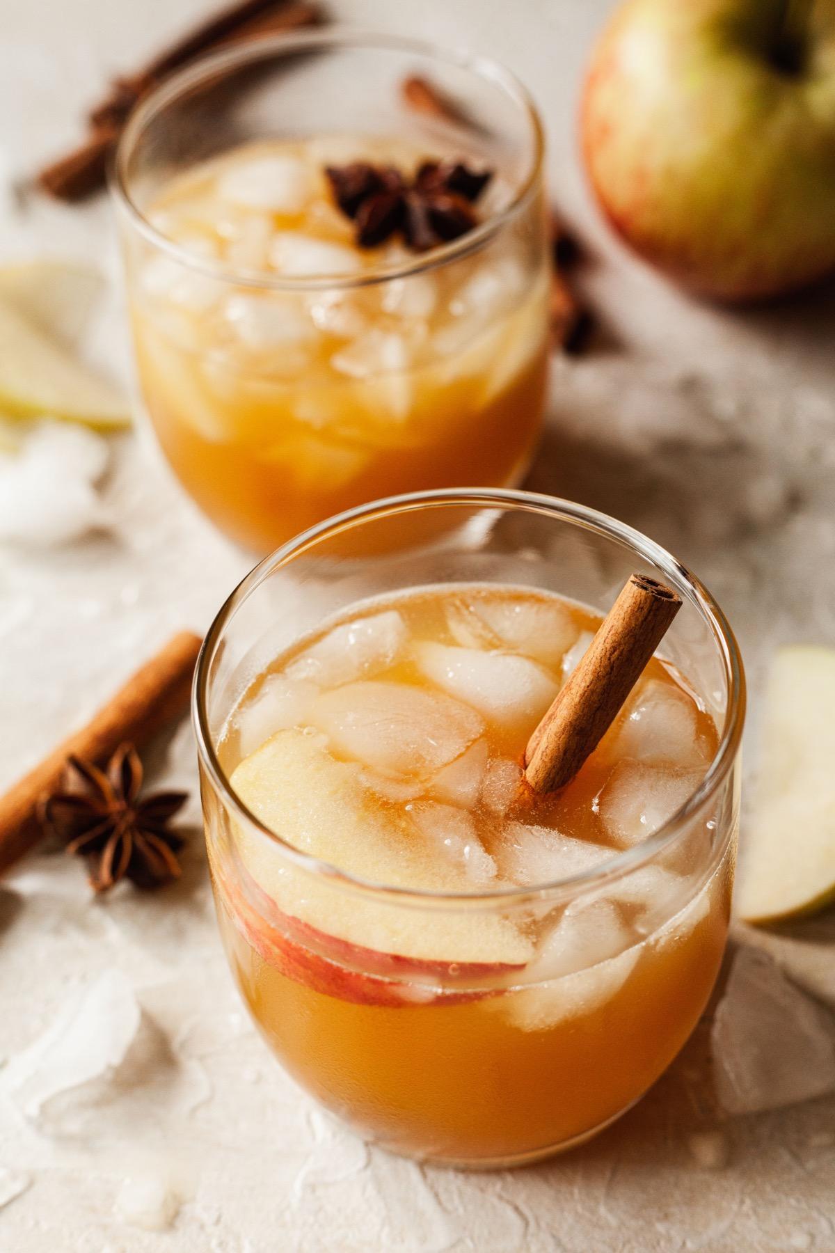two apple cider bourbon cocktails with cinnamon sticks