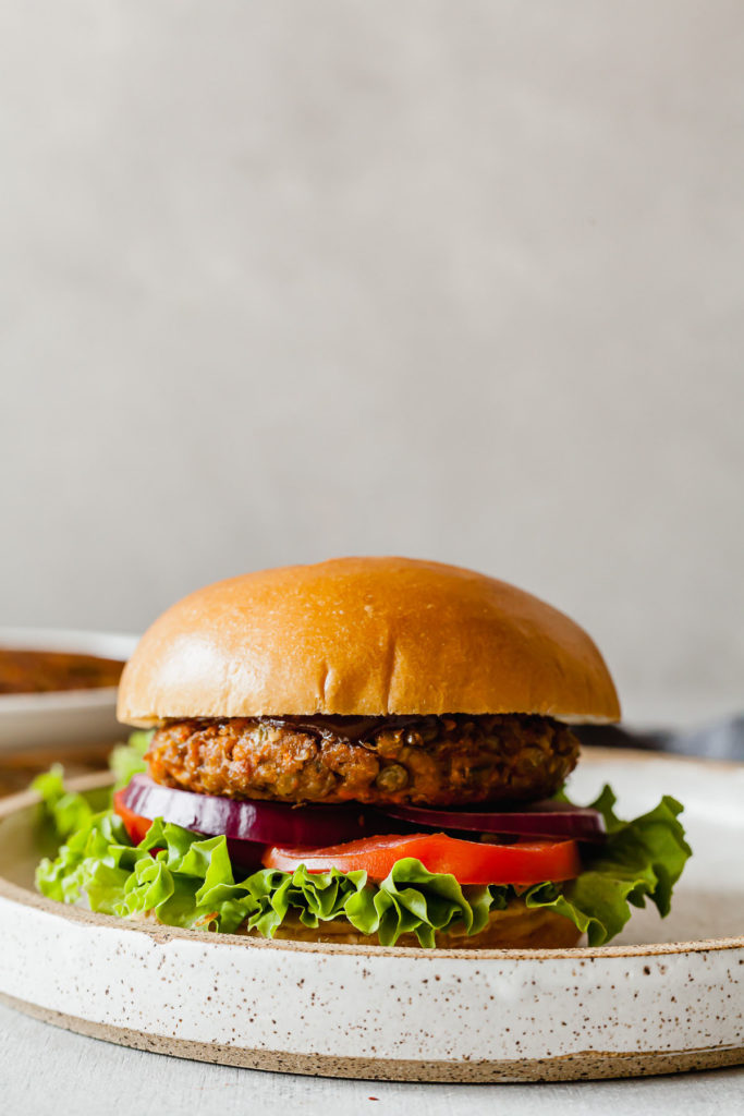 side view of a lentil veggie burger with onion, tomato, and lettuce