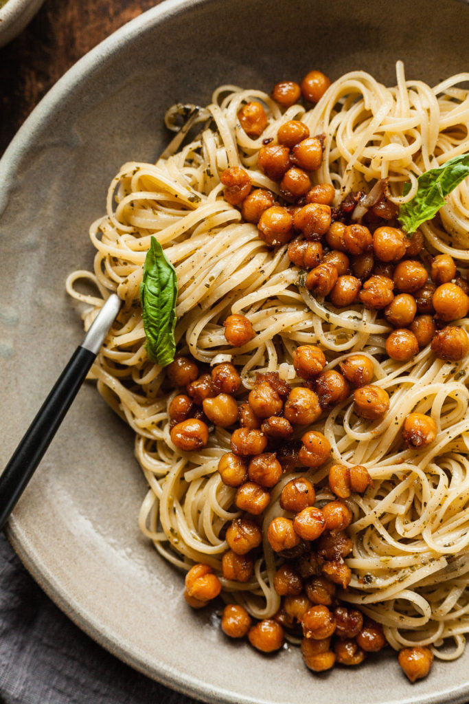 close up photo of pesto linguine with balsamic chickpeas on a plate with a fork