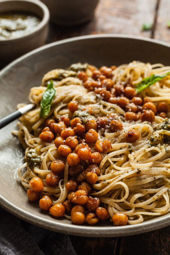 a plate of pesto pasta with cooked chickpeas, pesto, and basil