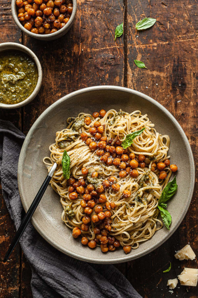a bowl of pesto linguine topped with roasted chickpeas